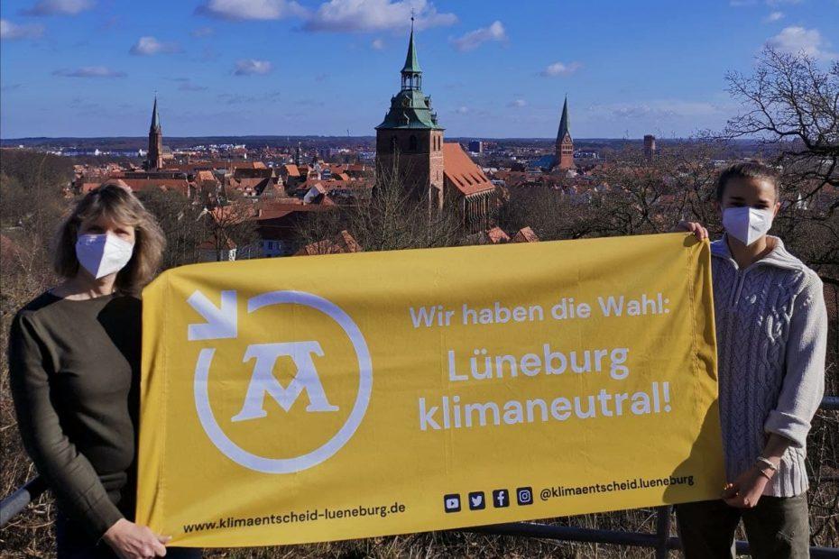 """Zwei Mitglieder halten gelbes Banner """"Wir haben die Wahl: Lüneburg klimaneutral!"""""""